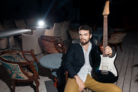 amp: stylish bearded man with electric guitar; hipster with amp sitting in chair;