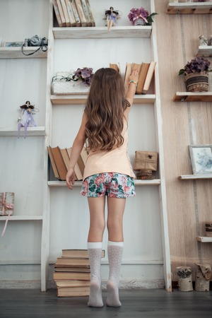 cute little girl searching interesting book with fairy tale;