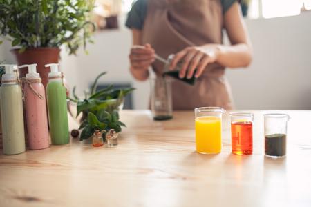 여자 나무 테이블에 손수 화장품을 만든다; 여성 다채로운 재료와 집에서 크림을 준비; 스톡 콘텐츠
