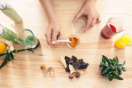 Donna fa cosmetici fatti a mano sul tavolo in legno; femmina preparare creme fatte in casa con ingredienti colorati; Archivio Fotografico - 67299213