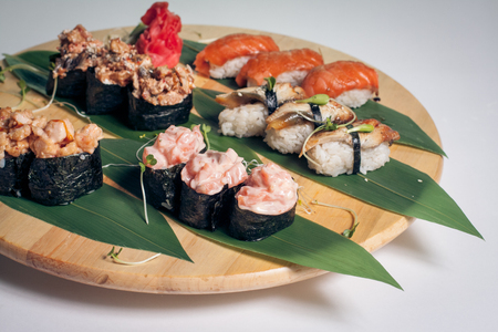 sushi set with gunkan on bamboo leaves; traditional asian sea food isolated;