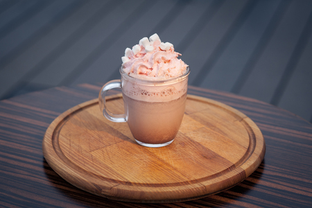 cup of cacao with pink and white marshmallow; glass with hot sweet cocoa;
