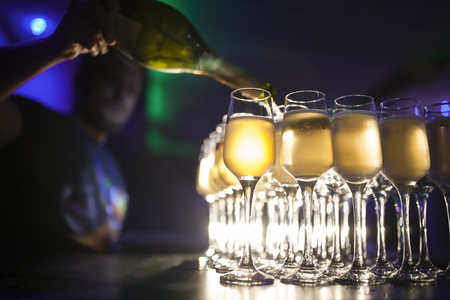 fill up: barman filling up glasses with wine; waiter pouring wineglasses with champagne or martini;
