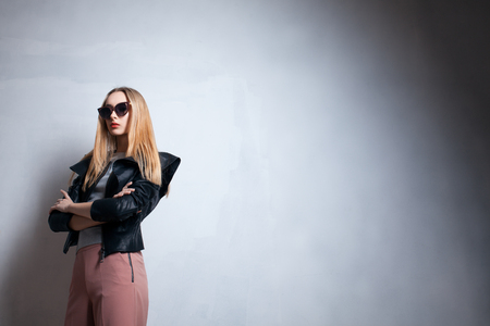 young blond model in sun glasses; fashion lady in sunglasses posing in studio; Stock Photo
