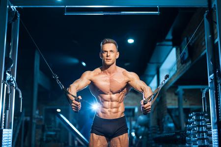 Sportler mit muskulösem Oberkörper trainiert im Fitnessstudio;