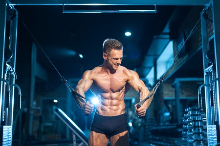 sportsman with muscular torso has workout in gym;