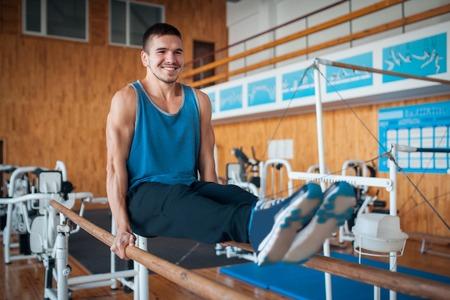 sportsman has workout with gymnastics bar; Imagens
