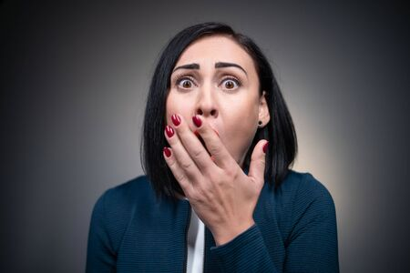 Ansiosa mujer morena preocuparse y morderse los dedos Foto de archivo