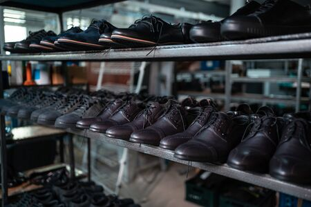 shelf with leather man shoes on modern footwear factory