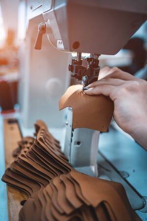 woman work with sewing machinery on shoe factory