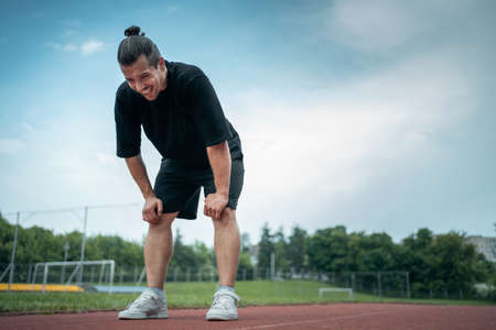 exhausted athlete resting on track after running or workout exercising outdoor 免版税图像