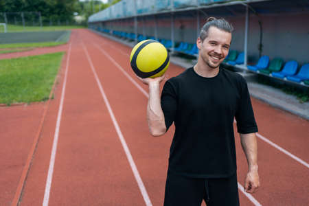 athlete and personal trainer with medicine ball has workout outdoor