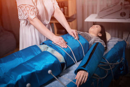 woman lying on body pressotherapy machine in beauty center Banco de Imagens