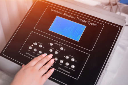 doctor setting up pressotherapy machine for slimming in spa salon
