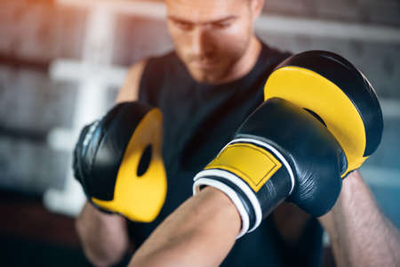 close up of man boxing sparring or fighting in boxing gloves at ring