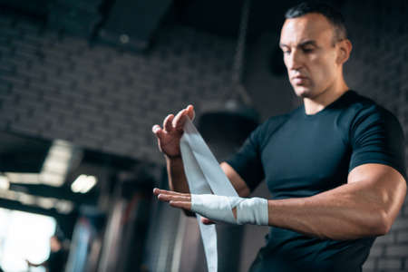 athletic boxer man bandage hand and preparing for training or fighting in gym
