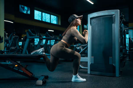 attractive athletic female in sportswear squat and have workout in gym