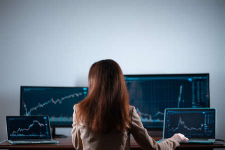 back view of female trader looking at monitor with stock exchange graph or chart