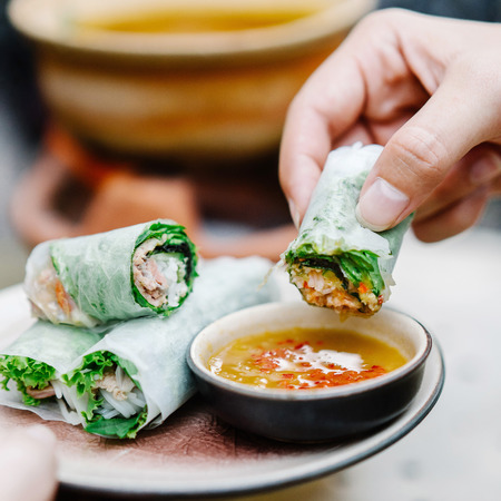 Hand dipping Vietnamese spring roll in sauce