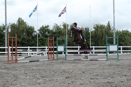 Man op paard springen over obstakel bij paardensportcentrum
