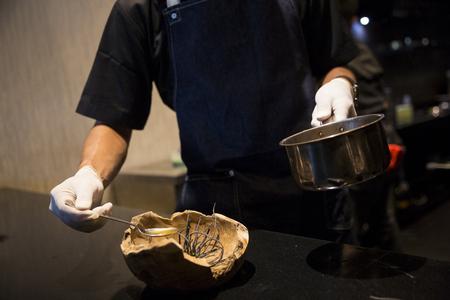 Chef-kok met witte handschoenen sudderen saus uit metalen pot voor het bereiden van voedsel in goed restaurant