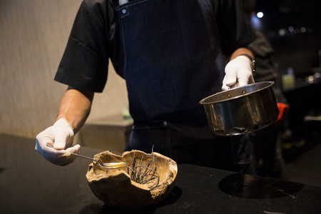 Chef with white gloves simmering sauce from metal pot for food dressing in fine restaurant