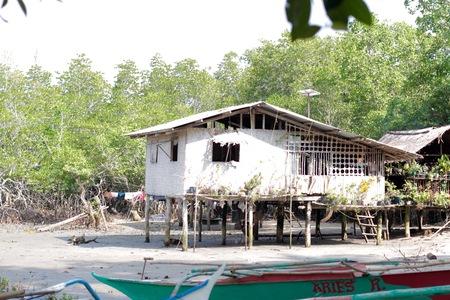 Oud wit dorpshuis in de jungle aan de rivier bij daglicht Stockfoto
