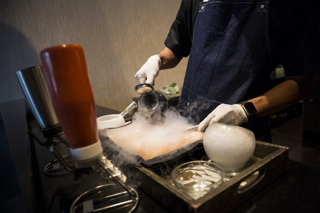 Hands with gloves pouring water from jug into smokey pan in a restaurant Stock Photo