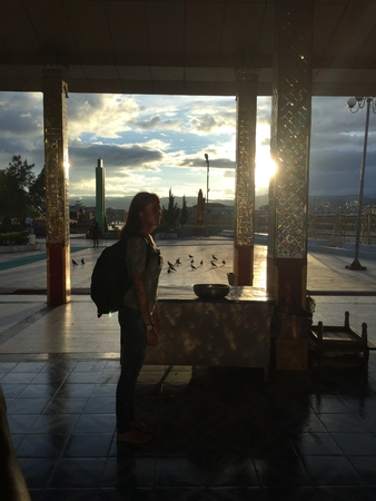 Lady standing inside building with pillars made of glass during dawn