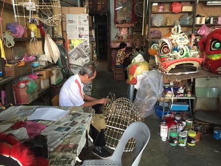 Chinese oude man en dame die leeuwenkop in een oude antiekwinkel maakt tijdens de dag