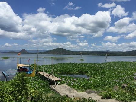 Inlemeer vulde met installaties met boot op de houten pier tijdens bewolkte blauwe hemeldag Stockfoto