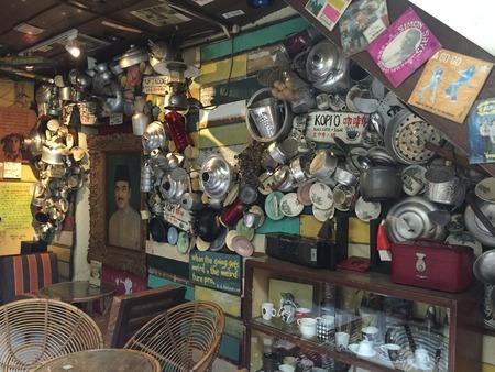 Oude koffiewinkel met potten en ketels op houten kleurrijke muur hangen
