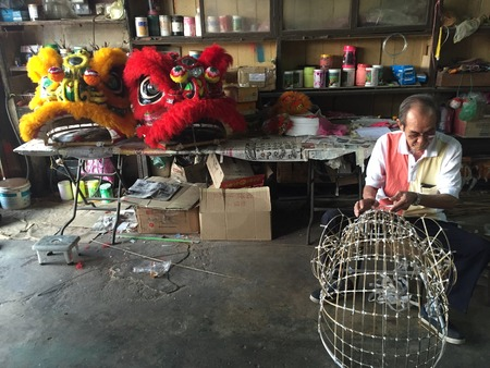 Chinese old man making lion head with red and yellow colored lion head displayed Editorial
