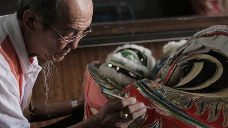 Oude man met witte baard schilderij op leeuwenkop met een penseel in een oude winkel