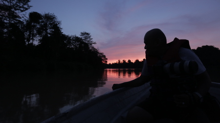 Man sitting on boat, looking over lake during sunset