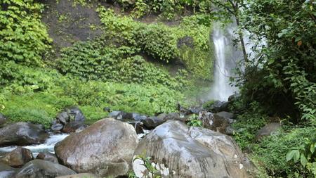 Waterval stroomt door reusachtige rotsen in het midden van het groene bos gedurende de dag