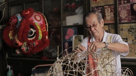 Chinese oude mens die leeuwenkop met rood gekleurd getoond leeuwhoofd maakt
