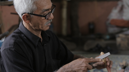 Old man using tool to shape wooden keris at Kuala Kangsar, Perak Editorial