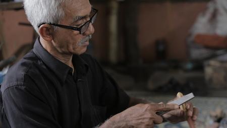 Oude mens die hulpmiddel met behulp van om houten keris in Kuala Kangsar, Perak gestalte te geven Redactioneel