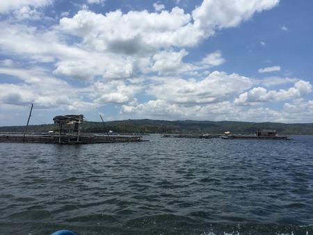 Strandmening van houten pier met bergmening en bewolkte blauwe hemel op dag