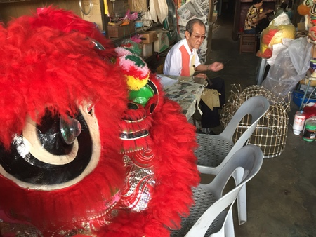 Chinese old man making lion head with red colored lion head displayed Editorial