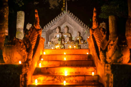godliness: buddha thai art with oil lamp in temple at night Editorial