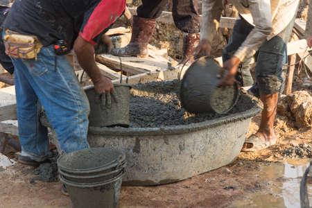 Worker casting concrete at construction site