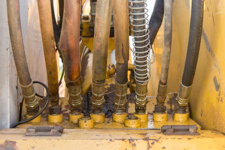 hydraulic hoses: Dirty hydraulic hoses of old backhoe