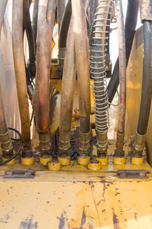 hoses: Dirty hydraulic hoses of old backhoe