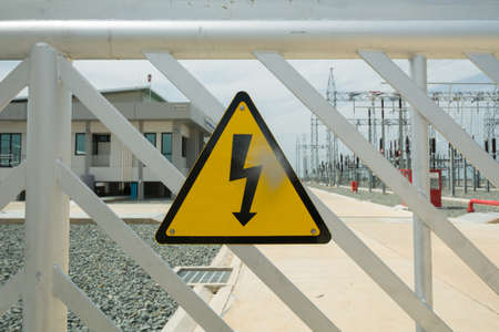 Danger sign high voltage on a mesh wire fence in front of substation Stock Photo