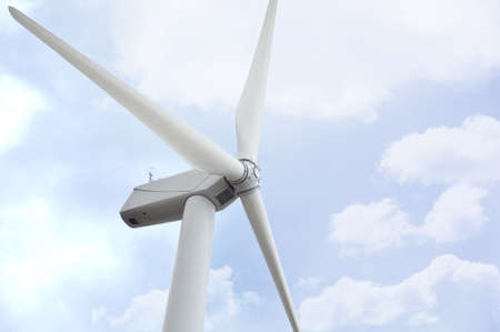 white wind turbine generating electricity on blue sky Stock Photo