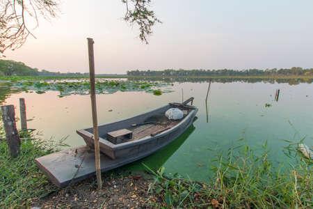 riverside trees: old boat on riverside in evenning sky background