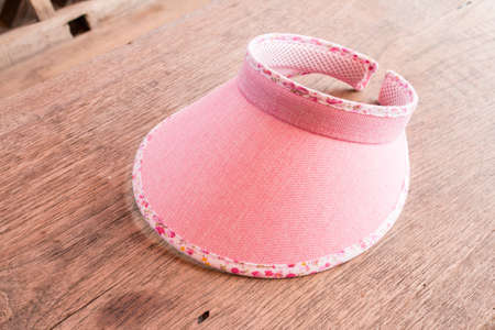 pink hat: Pink hat on wooden table