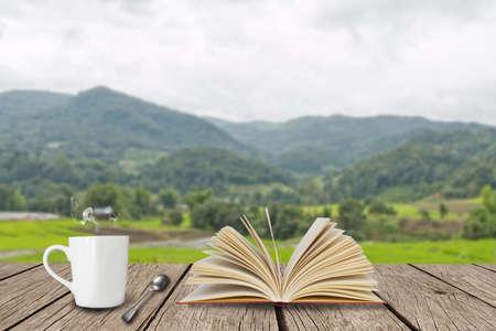 koffiekopje met open boek op houten plank Stockfoto